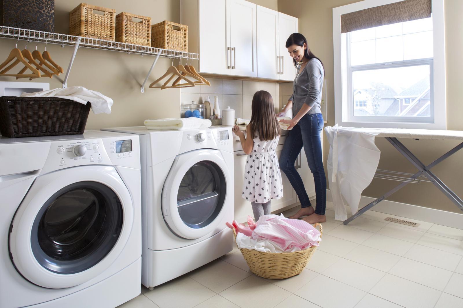 Madre y hija en el cuarto de lavado haciendo la colada