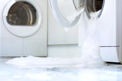 Maquina de lavar con la puerta abierta y chorreando agua
