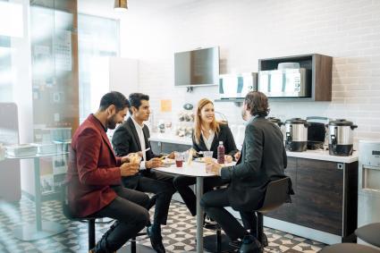 Empleados hablando y comiendo en la sala de descanso