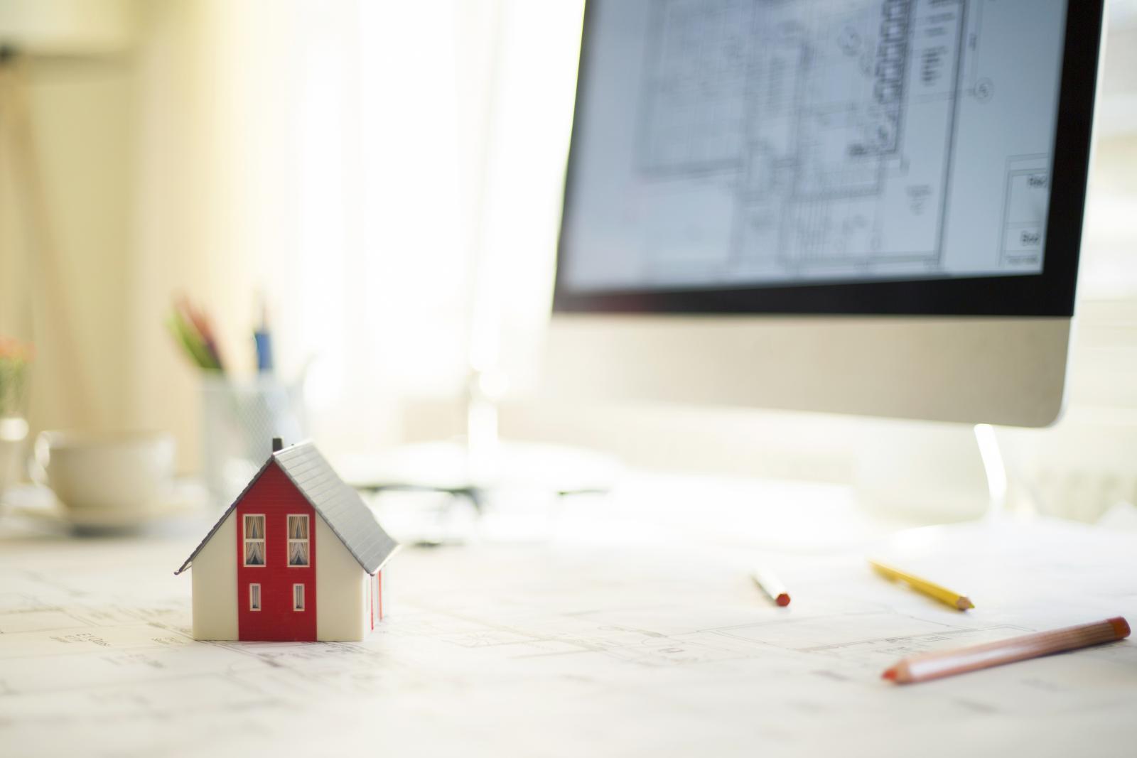 Casa en miniatura con los planos de la casa en el ordenador