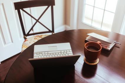 Ordenador, café y agenda encima de una mesa