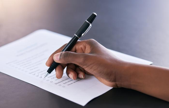 mujer marcando las tareas completadas en una lista de tareas