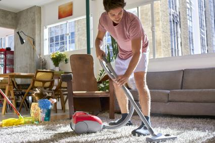 Hombre aspirando y limpiando la casa