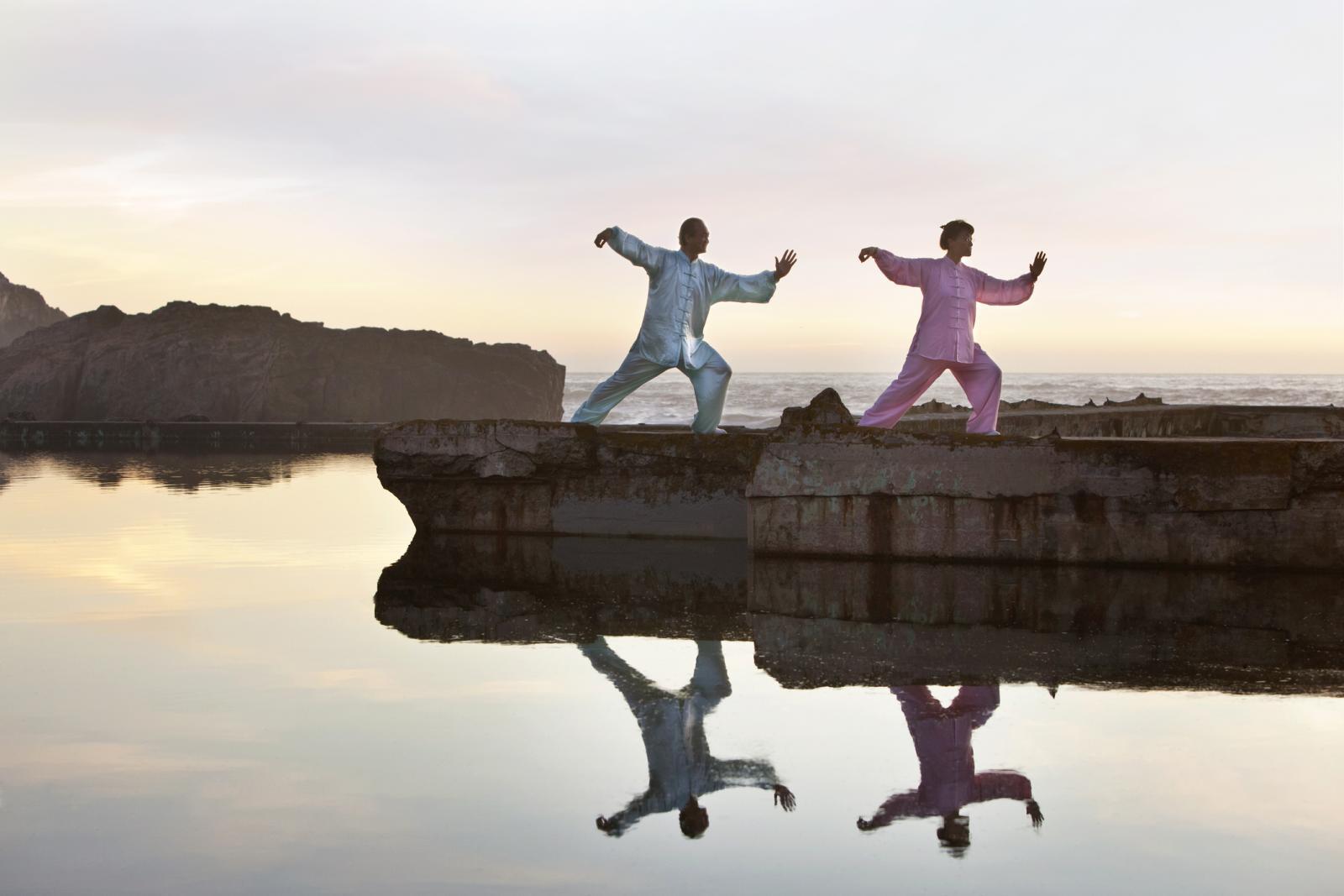 Mujer y hombre praticando Tai Chi afuera