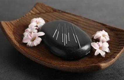 Agujas de acupuntura en una piedra de spa