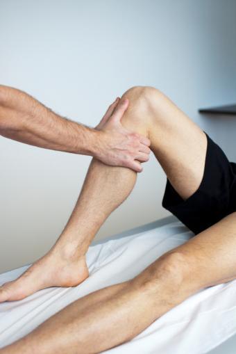 Massage therapist working on an athlete's leg