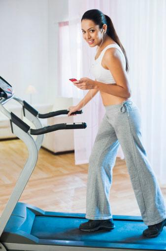 Woman walking on treadmill at home