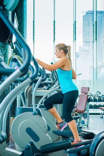 Woman using elliptical machine in gym