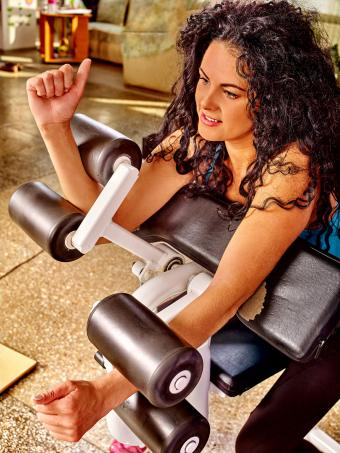Woman using bicep curl machine