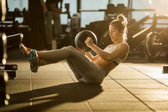woman doing situps with medicine ball