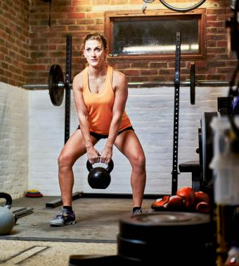Woman using kettle bell in home gym