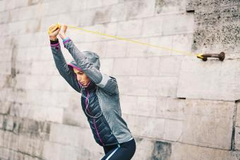 Young woman in sports wear training with elastic band on a wall outdoors