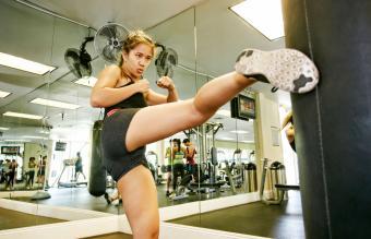 woman kicking punching bag in gymnasium