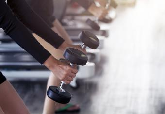 Female workout weight training with dumbbell at gym