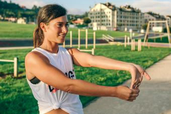 Woman doing wrist exercise in park