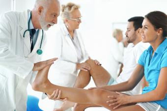 Doctor stretching woman's ankle