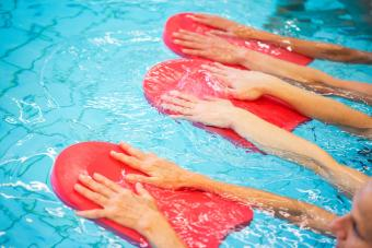 Women exercising in swimming pool with kickboards