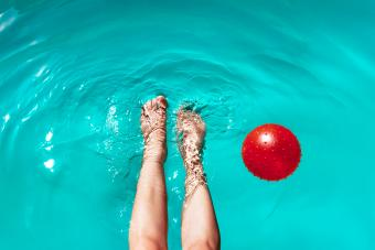 Woman With Ball Swimming In Pool