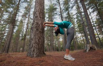 Runner stretching in forest
