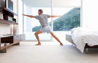 Mature man stretching in yoga stance in bedroom