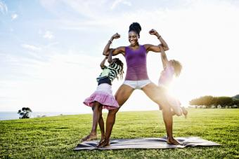 Woman lifting children with biceps in park