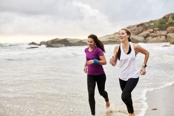 Females running barefoot on beach