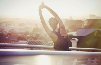 Female runner stretching arms on urban footbridge at sunrise