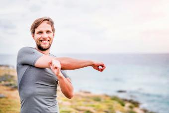 Happy sporty young man stretching on the coastline