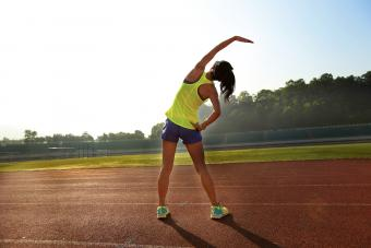Young woman runner stretching before run