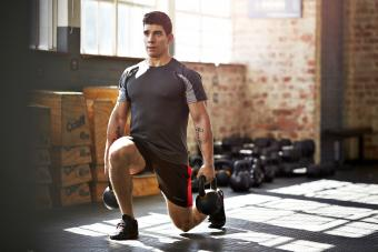 Gym instructor doing lunges with kettlebells