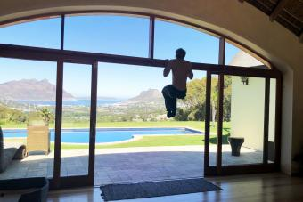 Young man uses a door frame for pull ups in his home