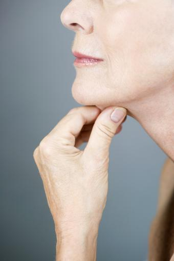 Senior woman massaging her neck