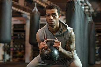 Young handsome Boxer Fighter training hard with a kettlebell in Gym Setting