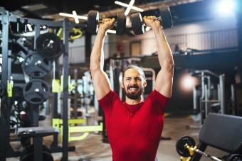 Young man lifting up dumbbells at the gym
