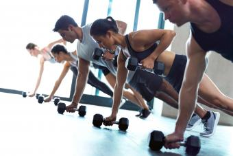 Fitness group working out with dumbbells in a gym