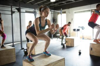 Woman jump squats in gym exercise class