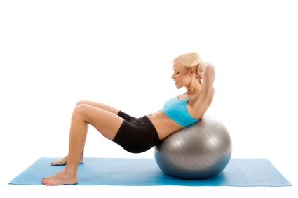 Woman doing crunches with an exercise ball.