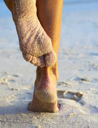 Woman scratching back of leg