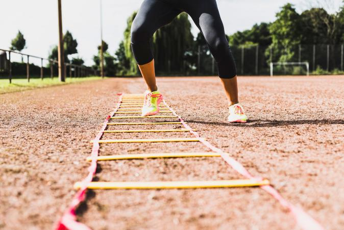 Woman exercising with agility ladder