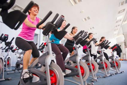 Women riding stationary bikes at gym