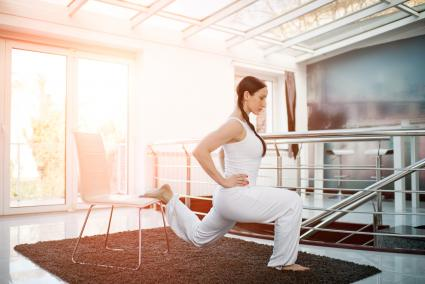 Woman performing chair lunges at home
