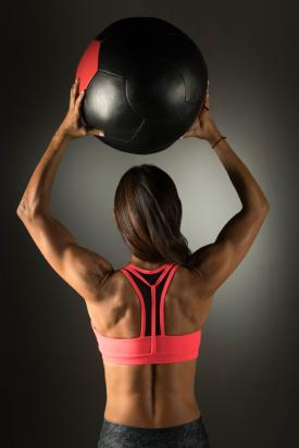 Woman holding medicine ball over head