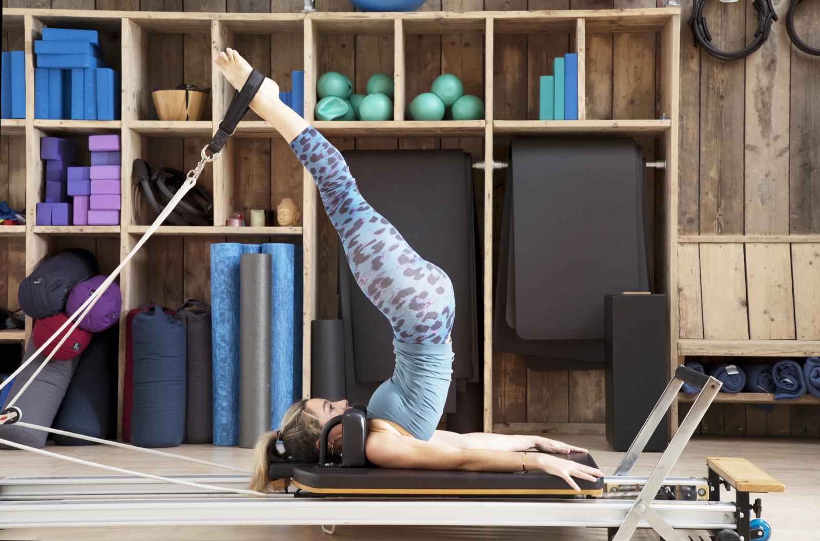 Woman on pilates reformer with legs in straps