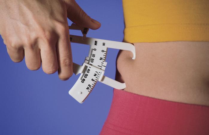 Woman measuring fat on waist