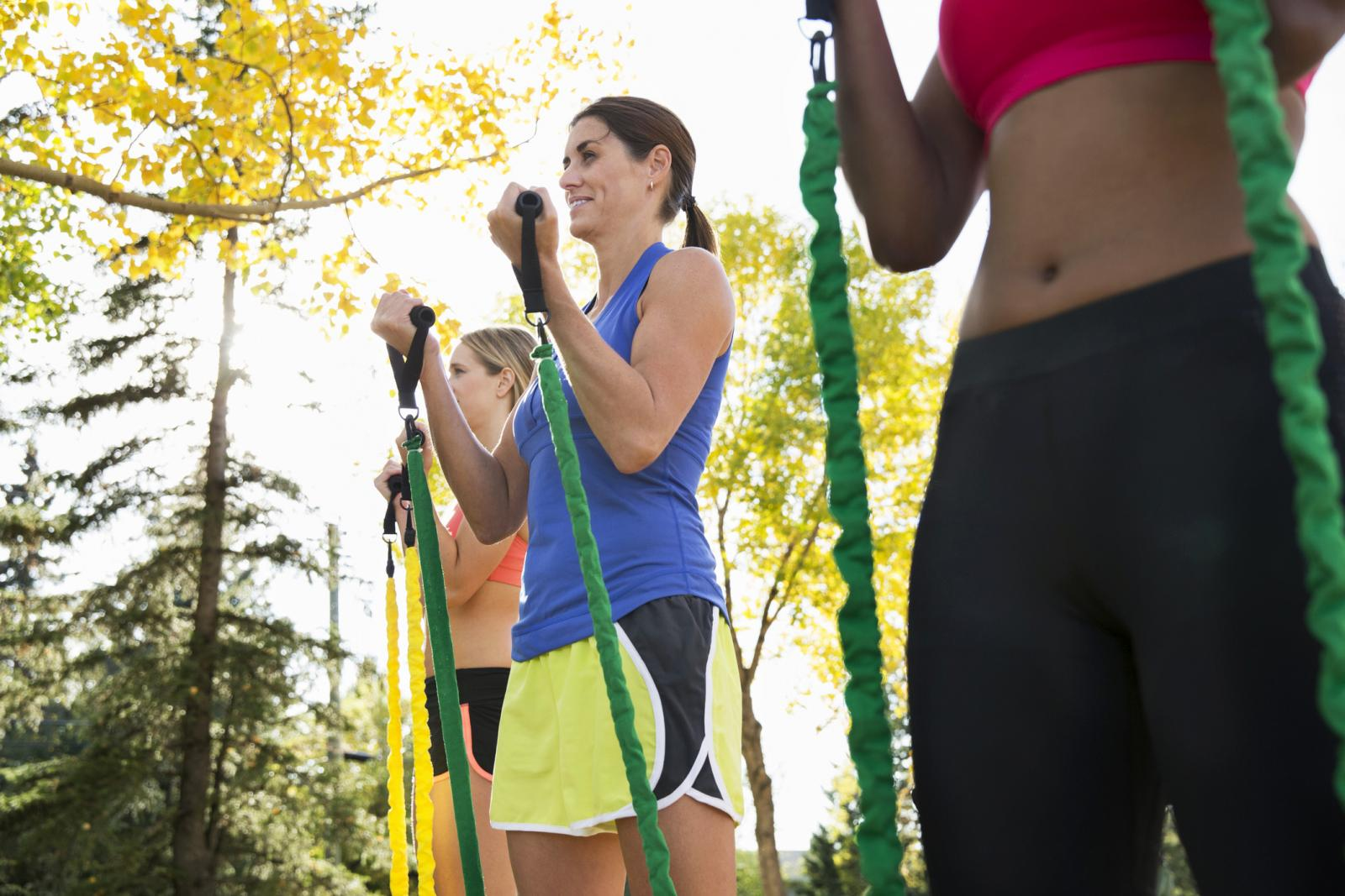 Women using resistance bands at outdoor fitness class