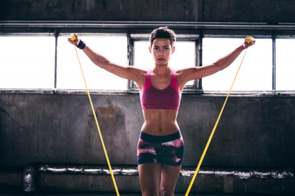 Young woman using a resistance band in gym exercises