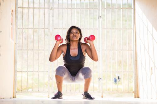 Woman performing dumbbell weighted squats