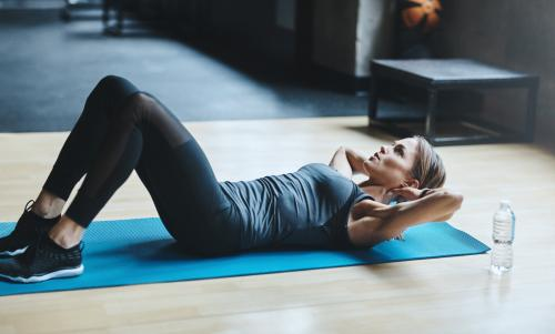 Woman doing abdominal crunches on a mat
