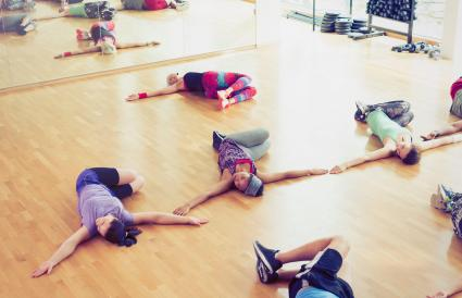 Exercise class doing twisted stretch in studio