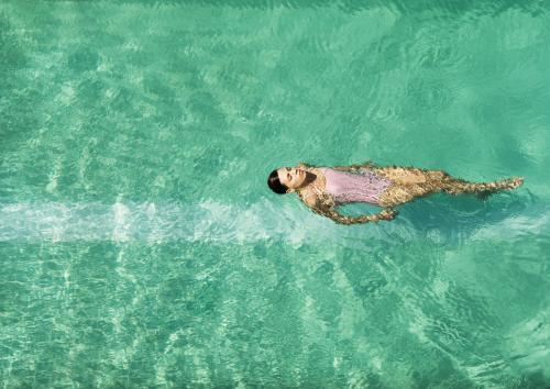 Overhead of woman floating in a pool